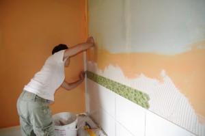 Artisan posant carrelage mural
